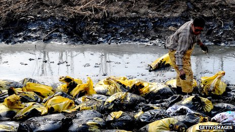 A Chinese worker cleans up a stream which has been polluted after an oil pipeline to a factory burst, in Beijing on March 28, 2012.