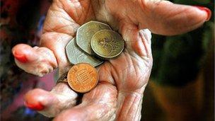 Elderly hand holding coins
