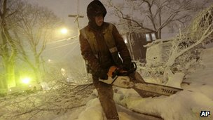 Workers clear a fallen tree from the road in New Bedford, Massachusetts 8 February 2013