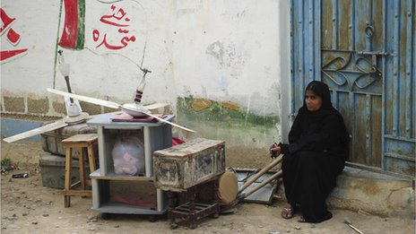 Woman sits outside her home after violence swept across neighbourhood