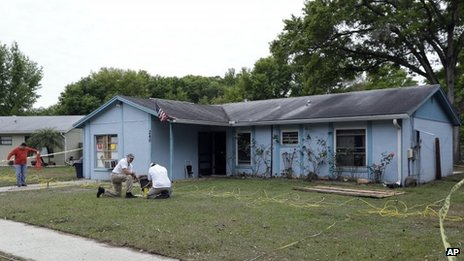 Engineers work in front of a home where sinkhole opened up underneath a bedroom and swallowed a man in Seffner, Florida 1 March 2013