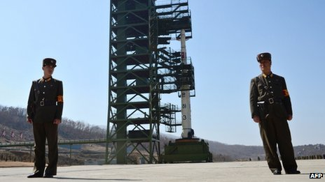 This file photo taken on April 8, 2012 shows two North Korean soldiers standing guard in front of the Unha-3 rocket at Tangachai -ri space center