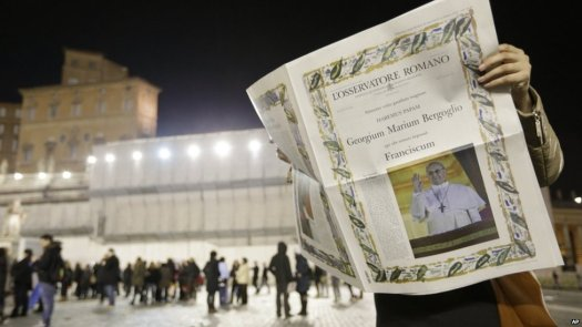A reader looks at the first edition of the Vatican newspaper L'Osservatore Romano after the election of Pope Francis