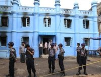 Police stand in front of a mosque and school dormitory that were damaged by a fire in Rangoon on 2 April 2013