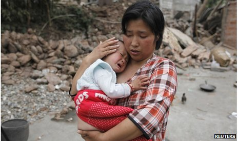 A woman comforts here baby in Longmen township, Sichuan (21 April 2013)