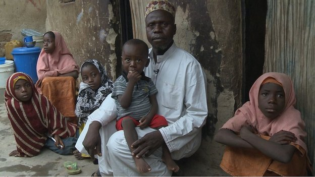 Usman Al Hassan and his children, including on his lap Abubarkar who contracted polio in 2013, on their home in the outskirts of Nigeria's capital, Abuja