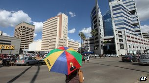 A woman with an umbrella bearing the image of US President Barack Obama in Harare, Zimbabwe, on 10 May 2013