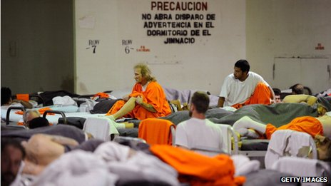Inmates at Chino State Prison, which houses 5500 inmates, crowd around double and triple bunk beds in a gymnasium that was modified to house 213 prisoners
