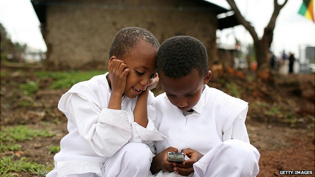 Ethiopian children play with a mobile phone