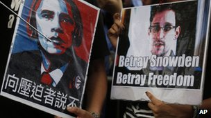 Protesters hold pictures of President Barack Obama, left, and Edward Snowden during a demonstration outside the Consulate General of the United States in Hong Kong 15 June 2013