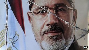 A portrait of ousted Egyptian President Mohammed Morsi is seen behind barbed wire during a demonstration by Morsi's supporters in Cairo, Egypt, Sunday, July 21, 2013.