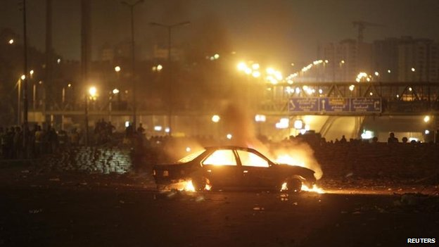A car burns during overnight protests in the Nasr city area east of Cairo
