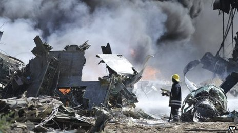 An AMISOM (African Union Mission in Somalia) firefighter attempts to extinguish a fire at the site of an airplane crash in Mogadishu, Somalia, 9 August, 2013.