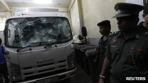 Army officers stand guard next to a damaged lorry at Fashion Bug's warehouse after an attack by unidentified men in Colombo March 28, 2013.