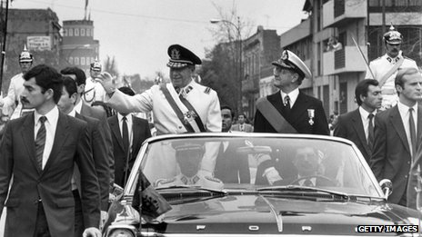 Black and white photo of Pinochet riding in a Ford convertible waving to onlookers
