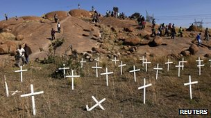 "Members of the mining community walk near crosses placed at the ""Hill of Horror"", where miners died during clashes with police in 2012"