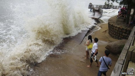 People watch as a storm surge hits the shores as Typhoon Usagi approaches Xiamen, Fujian province