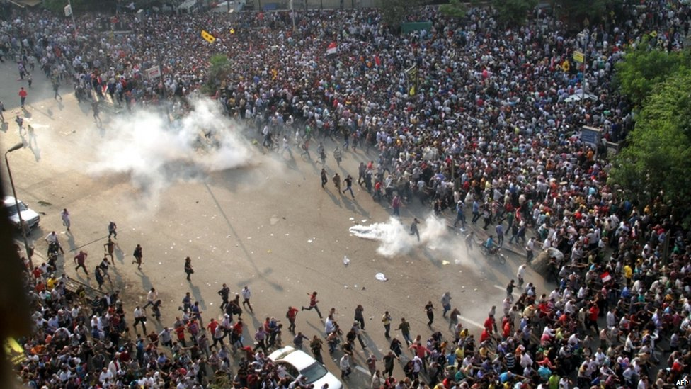 Egyptian Muslim Brotherhood and supporters of ousted president Mohammed Morsi run for cover from tear gas during clashes with riot police