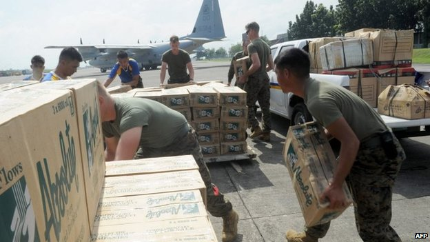 Philippine and US military personnel load relief goods for Tacloban on board a US C-130 plane for victims of Super Typhoon Haiyan that hit the central Philippines, at a military base in Manila on 11 November 2013