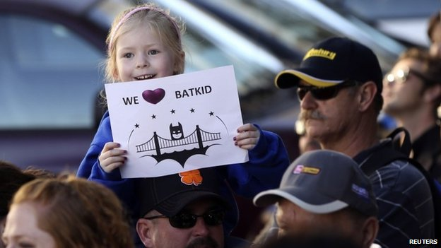 Kayla Fry holds a sign as she waits to see five-year-old leukemia survivor Miles Scott in San Francisco on 15 November 2013