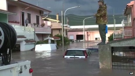 A rescue worker standing on wall overlooking flooded street with submerged cars after a cyclone brought severe flooding to Sardinia