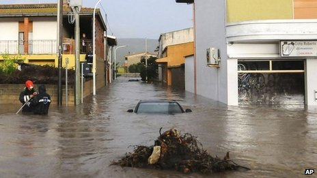 Rescuers work on a flooded street in the town of Uras, Sardinia. Photo: 18 November 2013