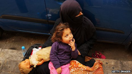 A Syrian woman from the city of Aleppo begs with her daughter Zahra (3) in a wealthy district of Beirut on November 16, 2013