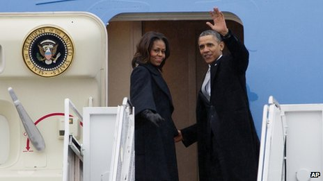 President Barack Obama, accompanied by first lady Michelle Obama, waves prior to boarding Air Force One before traveling to South Africa for a memorial service in honour of Nelson Mandela.