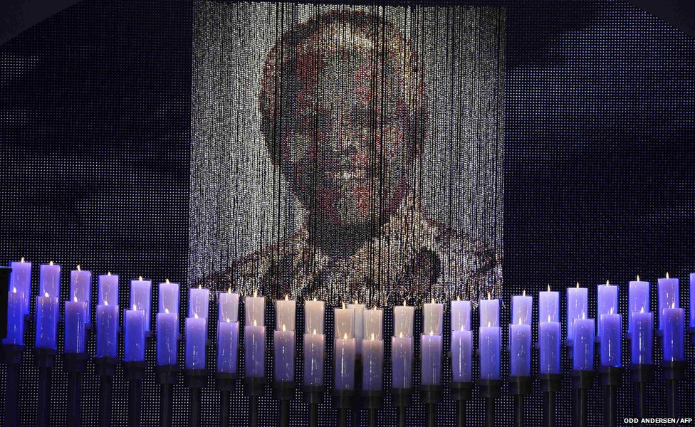 Candles are lit under a portrait of former South African President Mandela
