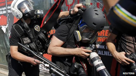 A Turkish riot policeman pushes a photographer during a protest at Taksim Square in Istanbul June 11, 2013