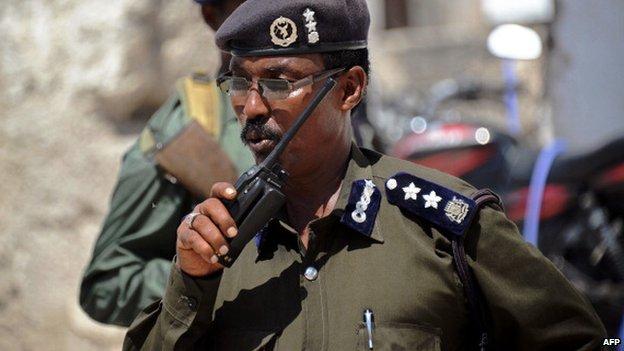 A Somali police officer talks on a radio in Mogadishu on 13 November 2013