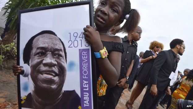 A crying girl holds a picture of late African superstar and king of Congolese rumbaTabu Ley Rochereau during his state funeral in Kinshasa on 9 December 2013