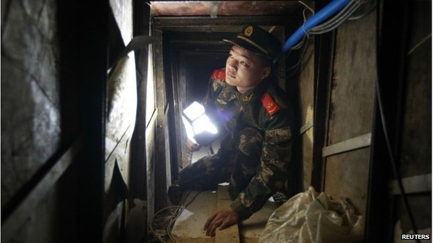 A policeman inspects a tunnel which was built by smugglers near the border of Hong Kong, in Changling village of Shenzhen, Guangdong province December 24