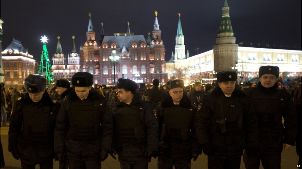 Russian police officers get ready to check people arriving at the Red Square ahead of the New Year's Eve festivities, in Moscow, Russia, Tuesday, Dec. 31, 2013.
