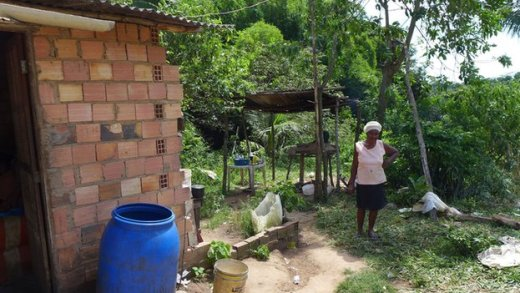 Woman in Rio dos Macacos cooks on an outdoor stove