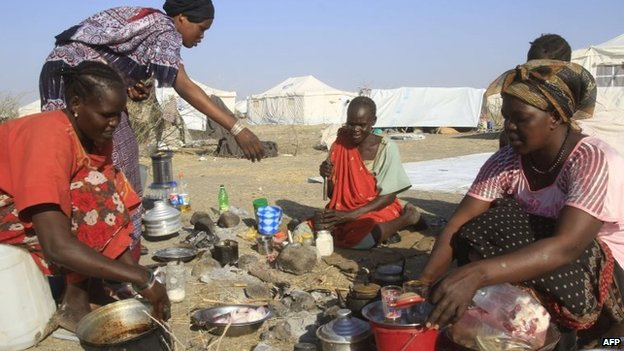 South Sudanese refugees cook on an open fire at a camp run by the Sudanese Red Crescent