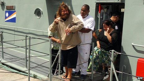 Jose Ivan walks with the help of a  nurse in Majuro