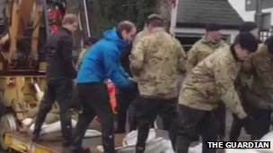 Princes Harry and William shift sandbags in Datchet, Berkshire