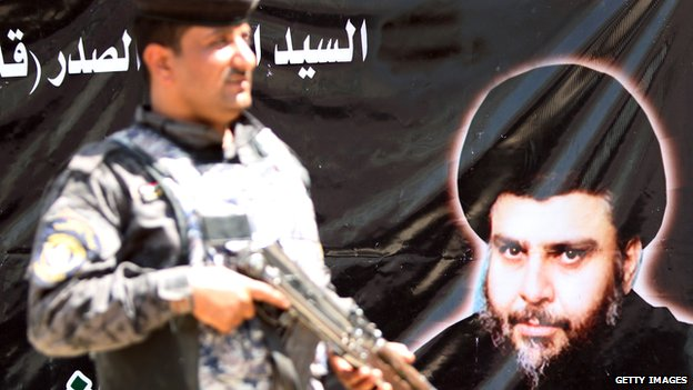 Iraqi solder in front of a poster of Moqtada Sadr in Baghdad (11 June 2012)