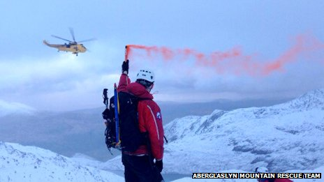 A  mountain rescue team member holds a red flare as the RAF helicopter approaches