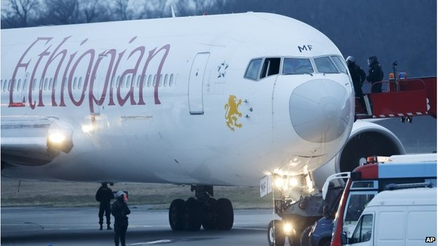Police stand around the aircraft after passengers were evacuated from a hijacked Ethiopian Airlines Plane on the airport in Geneva