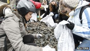 Anti-government protesters fill bags to build new barricades after clashes with riot police in Independence Square in Kiev