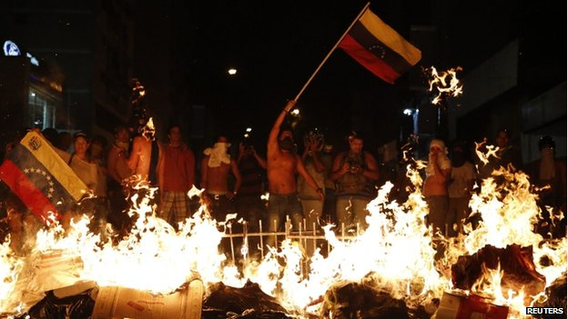 Anti-government protesters wave the Venezuelan flag in front of a burning barricade in Caracas (25 February 2014)