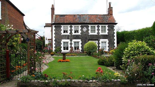 A curving swastika design on a pebble flint cottage near Aylsham in Norfolk