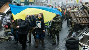 Members of a so-called Maidan self-defence unit march as they carry a coffin near a barricade in the centre of Kiev on 4 March 2014.
