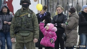A girl plays with a balloon near an armed man, believed to be Russian serviceman, near the gates of a Ukrainian military unit in the village of Perevalnoye outside Simferopol, 4 March 2014.