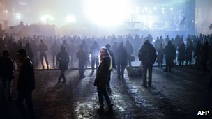 A woman looks on as people watch news on a large TV screen at the Independence square in central Kiev on 4 March 2014.