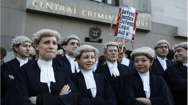 "Barristers outside the Central Criminal Court with a placard reading: ""Defend justice; defend legal aid."""