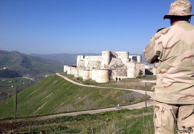 A Syrian soldier looks towards the Krak des Chevaliers castle near the Lebanese border, 20 March
