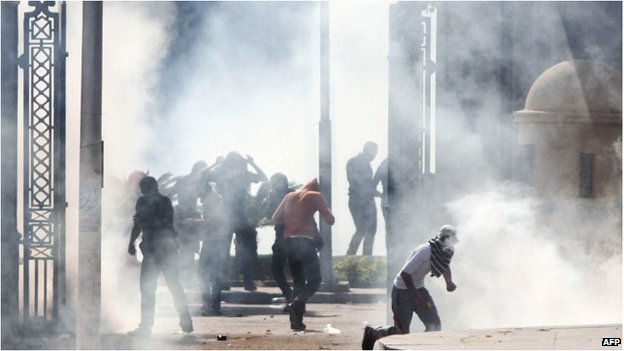 Egyptian Muslim Brotherhood students and supporters of ousted president Mohamed Morsi run through smoke during clashes with riot police following a demonstration outside Cairo University on March 26, 2014